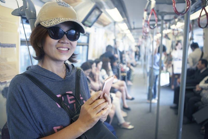 Gezicht van vrouw in hemeltrein met slim telefoon in hand gebruik voor het stadsleven en reizend thema stock foto's