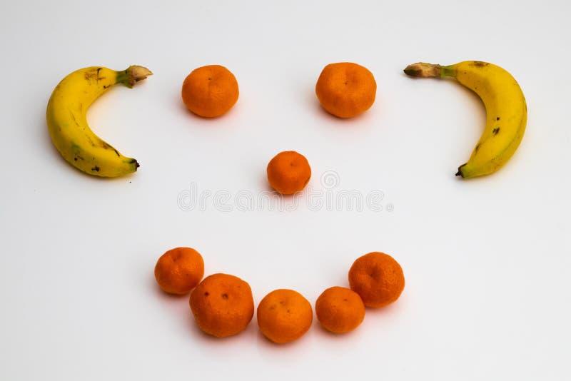 Gezicht van vruchten op witte achtergrond gezicht met verse vruchten wordt gemaakt die banaan, mandarin mandarijn royalty-vrije stock foto's
