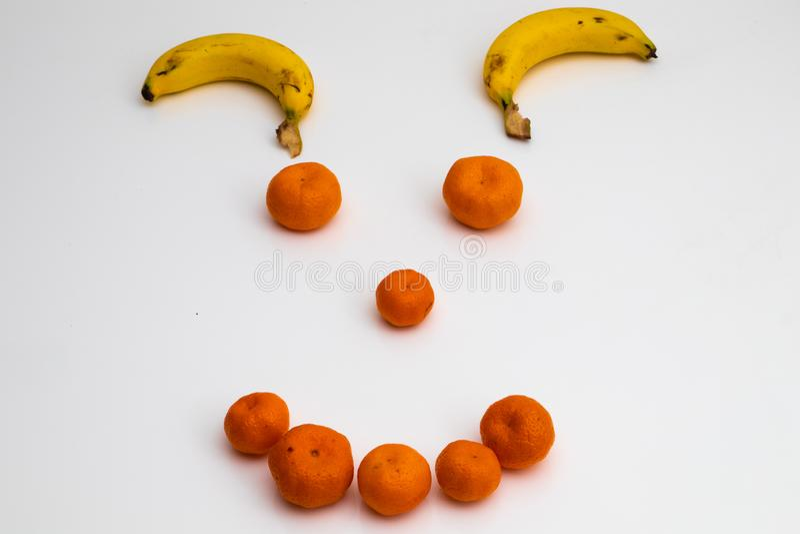 Gezicht van vruchten op witte achtergrond gezicht met verse vruchten wordt gemaakt die banaan, mandarin mandarijn stock afbeelding