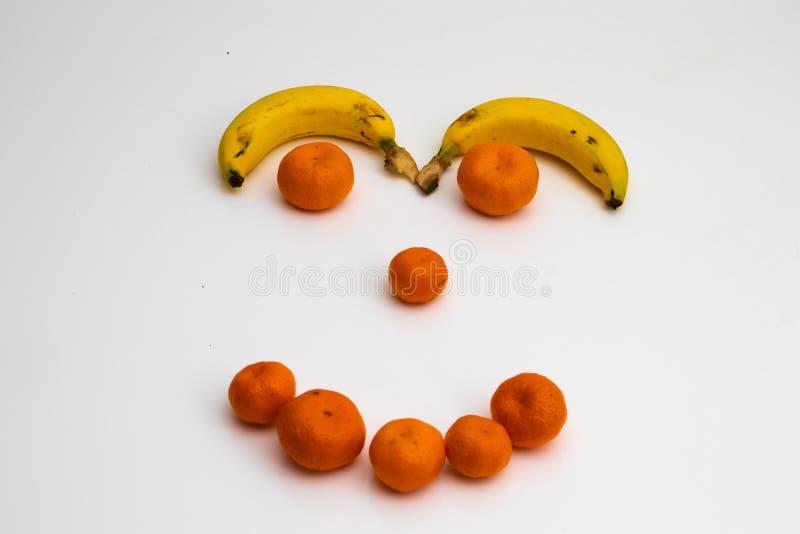 Gezicht van vruchten op witte achtergrond gezicht met verse vruchten wordt gemaakt die banaan, mandarin mandarijn royalty-vrije stock afbeelding