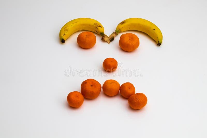 Gezicht van vruchten op witte achtergrond gezicht met verse vruchten wordt gemaakt die banaan, mandarin mandarijn stock fotografie