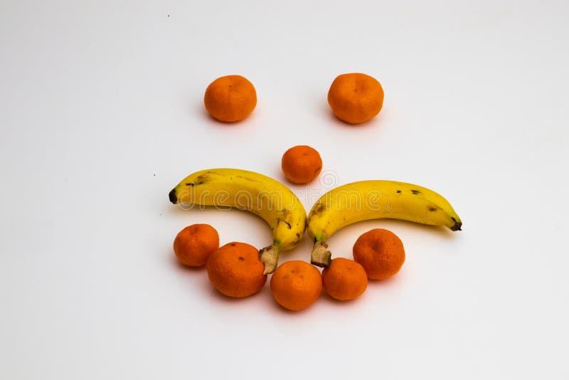 Gezicht van vruchten op witte achtergrond gezicht met verse vruchten wordt gemaakt die banaan, mandarin mandarijn royalty-vrije stock fotografie