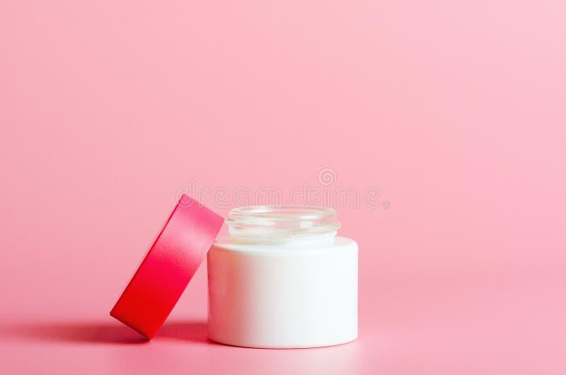 Gezichtsroom in witte kruik met een rode dekking op een roze achtergrond Schoonheidsmiddelen, schoonheid Minimale Samenstelling stock foto's