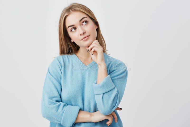 Gezichtsuitdrukkingen en emoties Nadenkend jong mooi meisje in de blauwe hand van de sweaterholding onder haar hoofd, die twijfel stock afbeelding