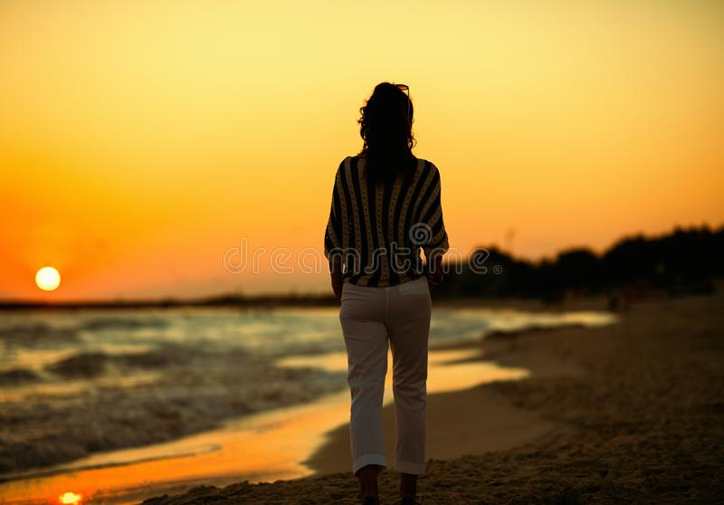 Gezien van achter modieuze vrouw op strand in avond het lopen stock afbeeldingen