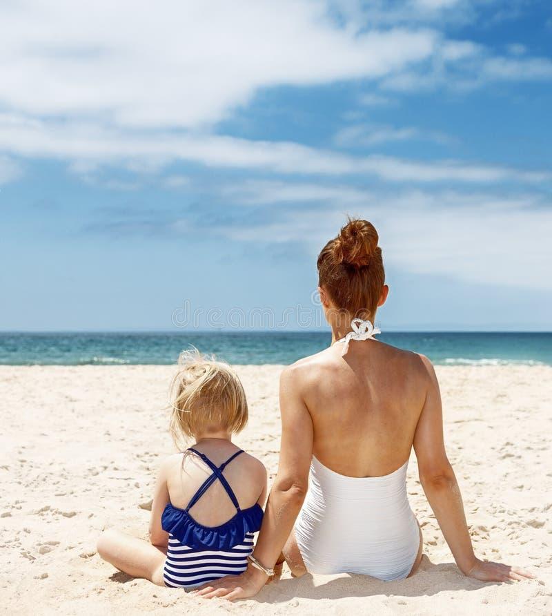 Gezien van achter moeder en kind die in zwempakken bij strand zitten stock foto's