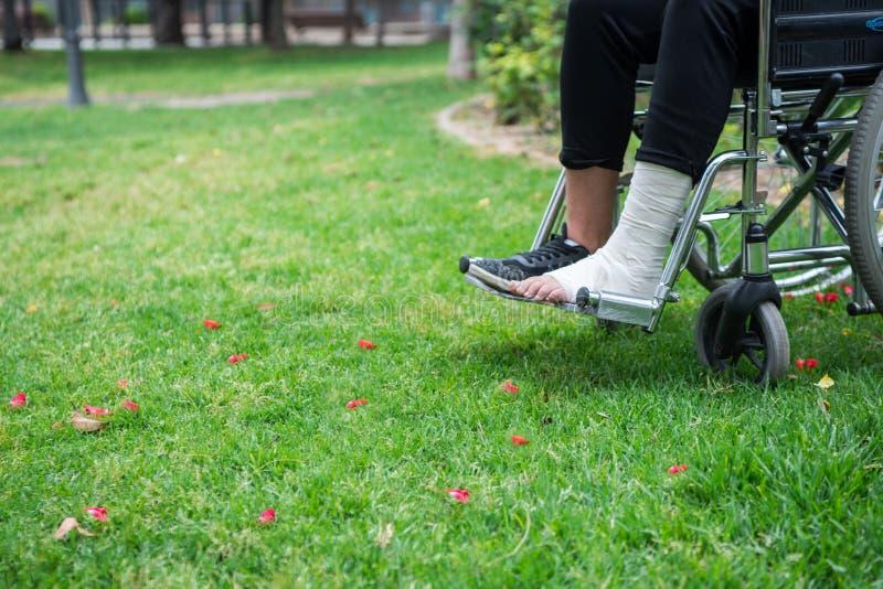 Gezien van boven voeten in een rolstoel Voet met verstuiking op grasbodem stock foto