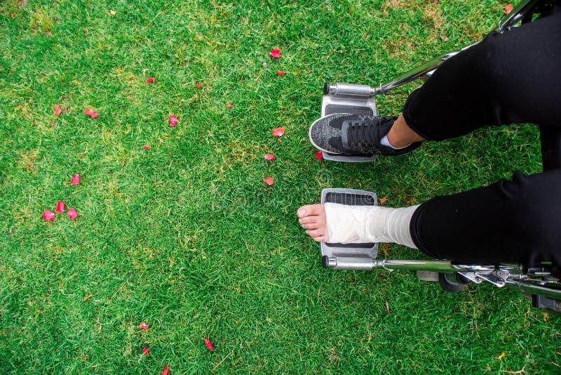 Gezien van boven voeten in een rolstoel Voet met verstuiking op grasbodem stock afbeeldingen