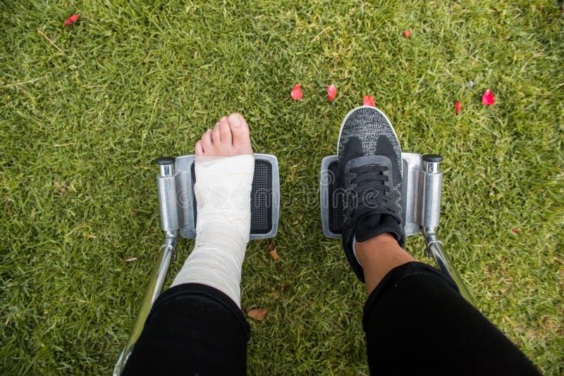 Gezien van boven voeten in een rolstoel Voet met verstuiking op grasbodem stock afbeelding