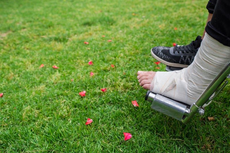 Gezien van boven voeten in een rolstoel Voet met verstuiking op grasbodem stock foto's