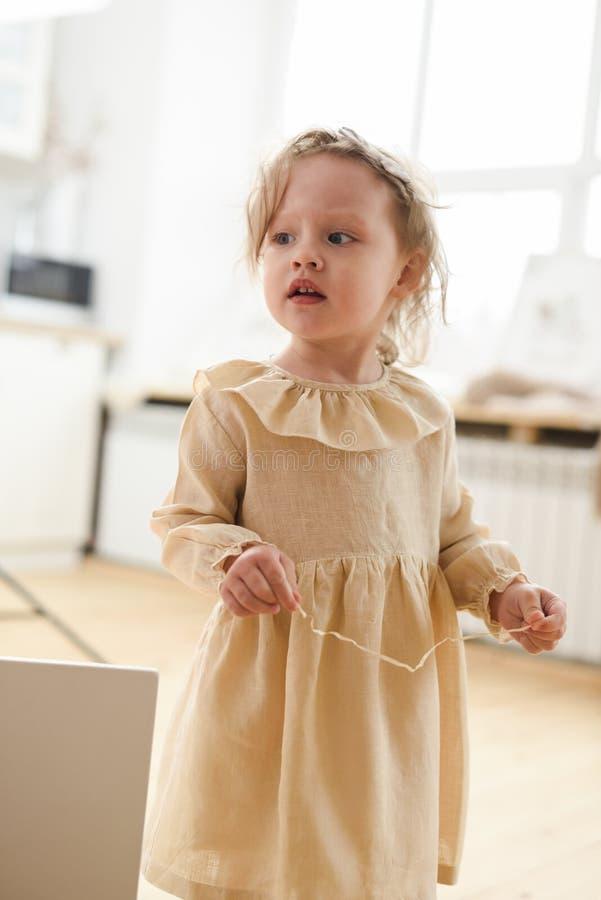 Gezinsbeginsel en begrip 'kind' Cute toddler girl in linnenjurk die aandachtig zijwaarts kijkt in een lichtvrije kamer royalty-vrije stock foto's