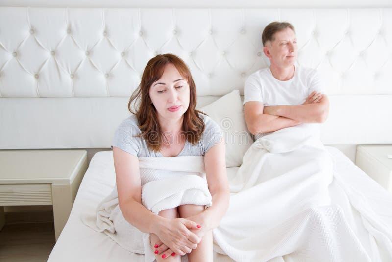 Gezinslevenconcept Problemen in verhoudingen Middenleeftijdspaar in slaapkamer Man en vrouw in bed Ruzie en verstoorde emoties stock fotografie