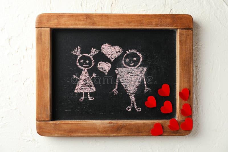 Gezogene Paare mit Herzen auf kleiner Tafel lizenzfreies stockfoto