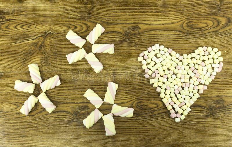 Gezogenes Herz und Schneeflocken mit Eibischen auf hölzernem backround lizenzfreies stockbild