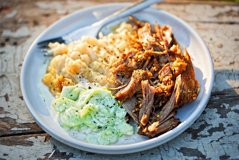 Gezogenes, reifes Schweinefleisch, mit gestampften gebratenen Kartoffeln und Gurken- und Sauerrahmsalat stockfotos