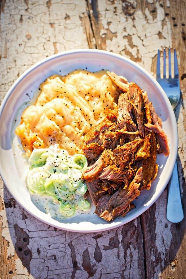 Gezogenes, reifes Schweinefleisch, mit gestampften gebratenen Kartoffeln und Gurken- und Sauerrahmsalat stockbild