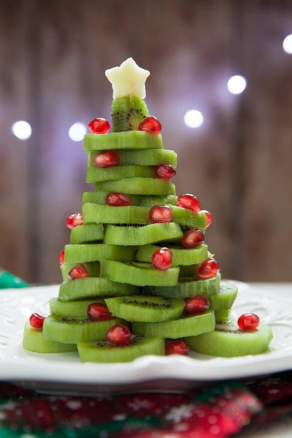 Gezond dessertidee voor jonge geitjespartij - de grappige eetbare Kerstboom van de kiwigranaatappel royalty-vrije stock afbeelding