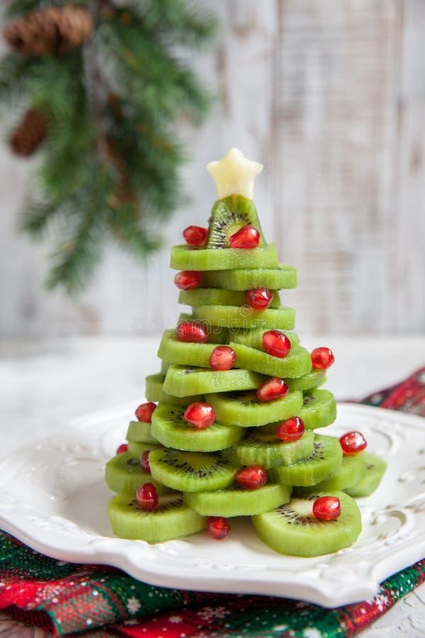 Gezond dessertidee voor jonge geitjespartij - de grappige eetbare Kerstboom van de kiwigranaatappel stock fotografie