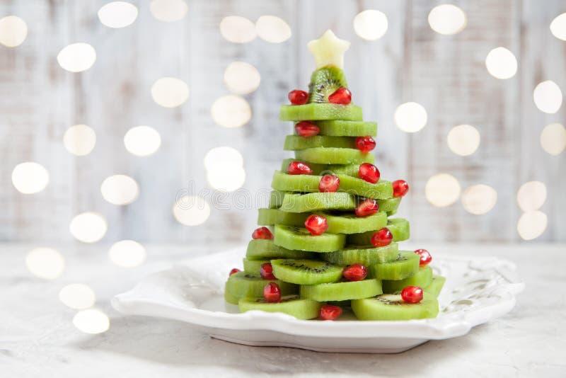 Gezond dessertidee voor jonge geitjespartij - de grappige eetbare Kerstboom van de kiwigranaatappel royalty-vrije stock foto