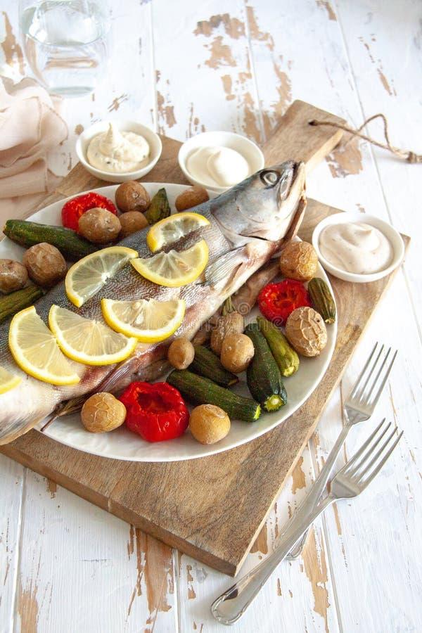 Gezond diner: zalm met groenten en citroen wordt gebakken die stock afbeeldingen