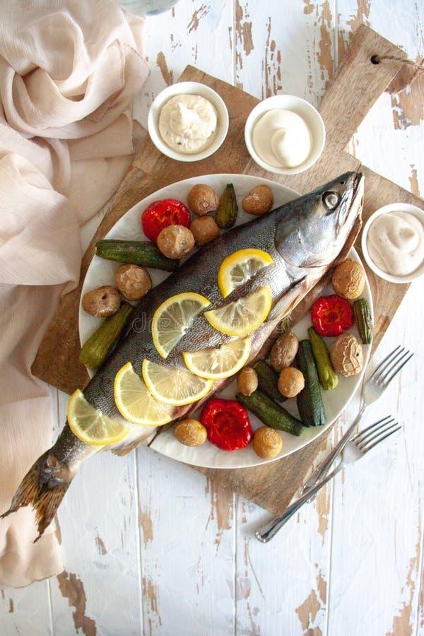 Gezond diner: zalm met groenten en citroen wordt gebakken die royalty-vrije stock foto's