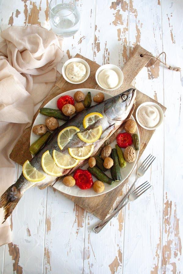 Gezond diner: zalm met groenten en citroen wordt gebakken die stock foto's