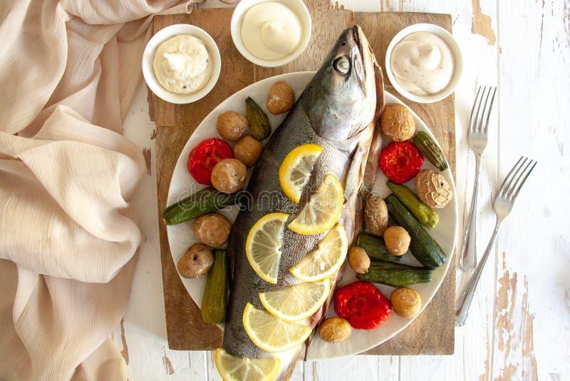 Gezond diner: zalm met groenten en citroen wordt gebakken die royalty-vrije stock foto