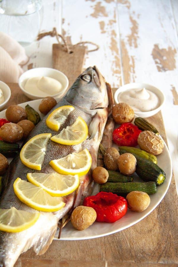 Gezond diner: zalm met groenten en citroen wordt gebakken die royalty-vrije stock afbeeldingen
