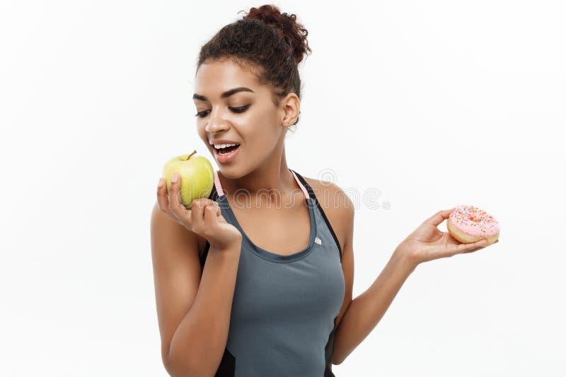 Gezond en dieetconcept - Mooie sportieve Afrikaanse Amerikaan neemt een besluit tussen doughnut en groene appel geïsoleerde stock afbeelding
