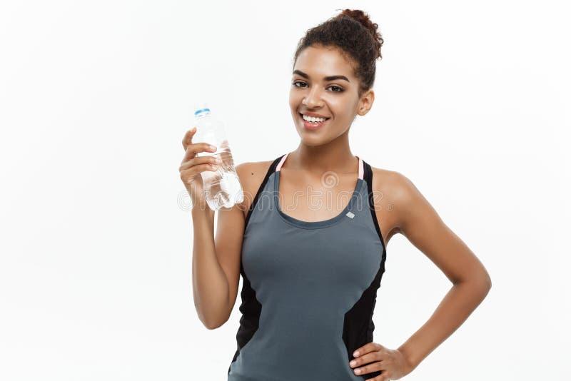 Gezond en geschiktheidsconcept - het mooie Afrikaanse Amerikaanse meisje in sport kleedt daarna het houden van plastic waterfles royalty-vrije stock foto