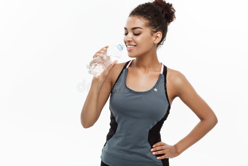 Gezond en Geschiktheidsconcept - het mooie Afrikaanse Amerikaanse meisje in sport kleedt drinkwater daarna door plastic fles stock foto's