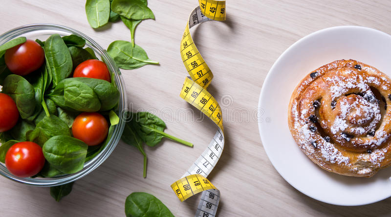 Gezond en ongezond voedsel - salade met spinazie en tomaten, me stock afbeelding