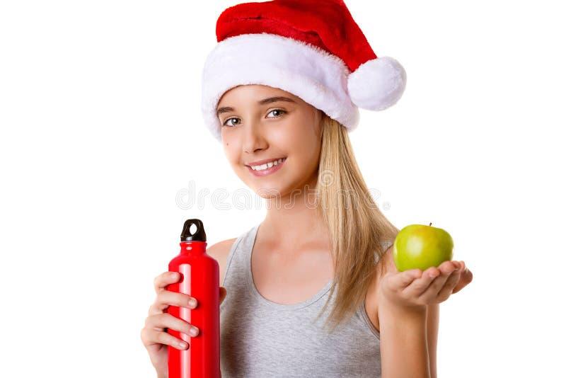 Gezond geïsoleerd geschiktheidsmeisje in de holdingsappel van de Kerstmanhoed en rode fles, royalty-vrije stock fotografie