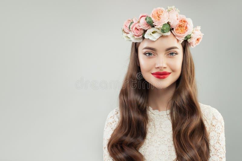 Gezond Glimlachend ModelWoman met Duidelijke Huid, Lang Krullend Haar, Make-up en Bloemen op Witte Achtergrond royalty-vrije stock afbeeldingen