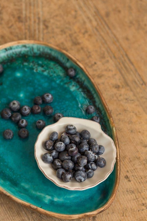 Gezond het Eten Concept Bosbessen in kleine witte ceramicepla stock afbeeldingen