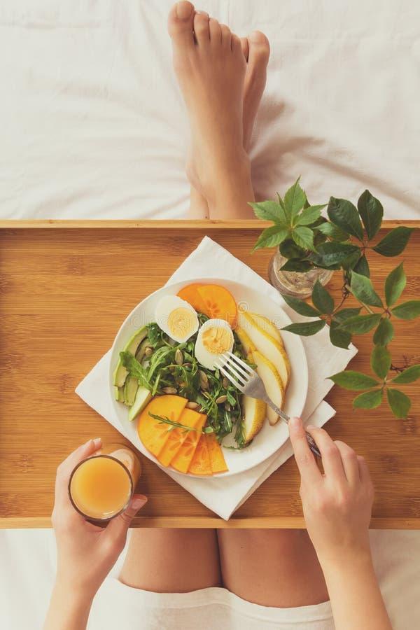 Gezond het Eten Concept Vrouw die ontbijt in bed heeft royalty-vrije stock fotografie