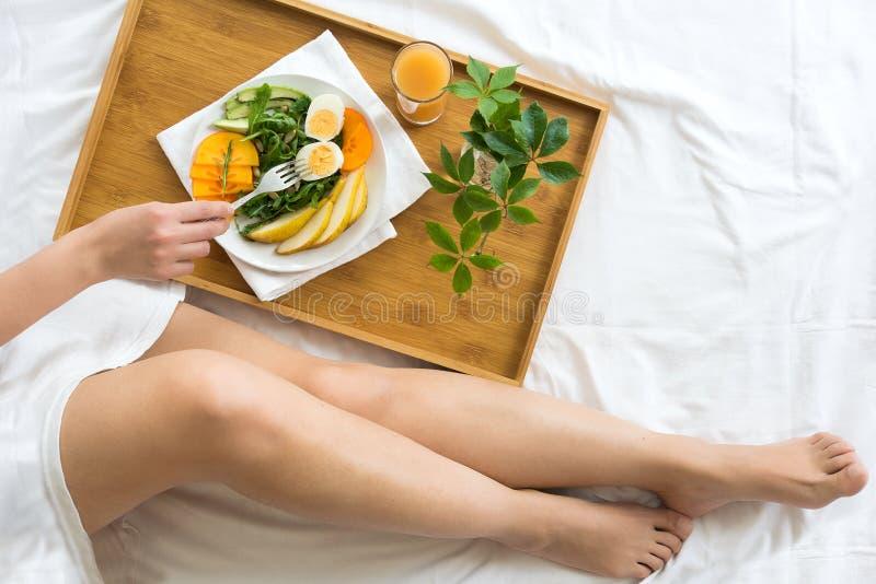 Gezond het Eten Concept Vrouw die ontbijt in bed heeft stock afbeelding