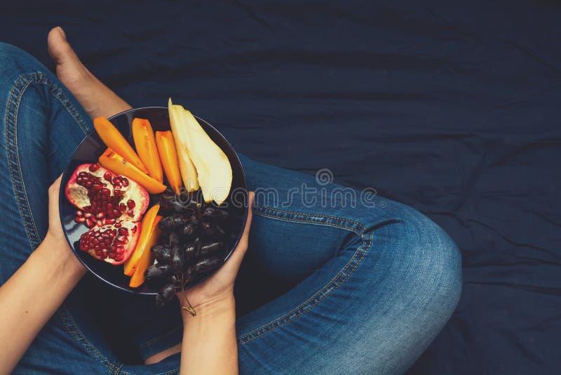 Gezond het Eten Concept Vrouwen` s handen die plaat met peren, druiven, dadelpruim en granaatappelvruchten houden royalty-vrije stock fotografie