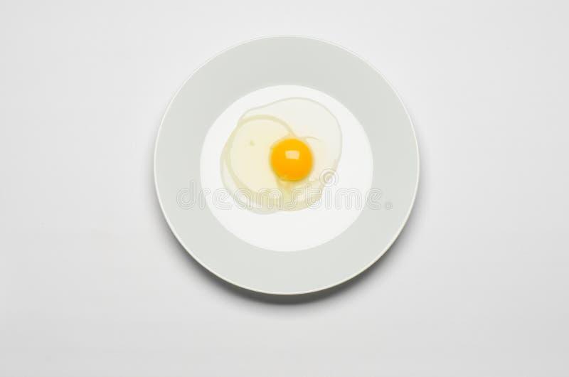 Gezond het eten en Ontbijtonderwerp: het ruwe ei legt op een witte plaat op een wit geïsoleerde achtergrond in studio hoogste men stock fotografie