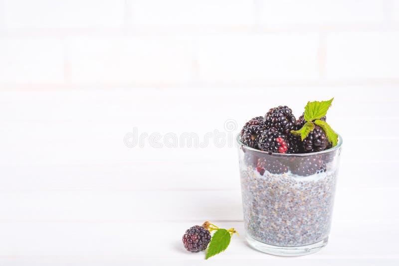 Gezond het eten en het op dieet zijn concept Eigengemaakte witte chiapudding met verse bessen voor ontbijt op een lichte keukenli stock afbeeldingen