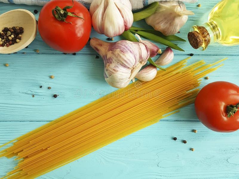 Gezond het voedseldieet van de spaghettiolie, de zwarte peper van de knoflooktomaat op een houten blauw royalty-vrije stock fotografie