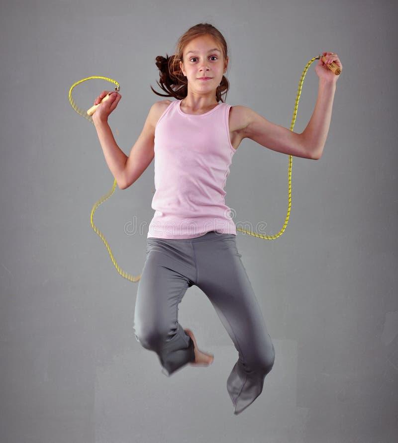 Gezond jong spiertienertouwtjespringen in studio Kind die met het springen hoog op grijze achtergrond uitoefenen stock afbeeldingen