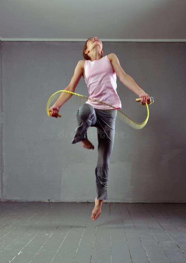 Gezond jong spiertienertouwtjespringen in studio Kind die met het springen op grijze achtergrond uitoefenen royalty-vrije stock afbeelding