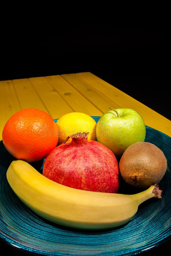 Gezond kleurrijk fruit met inbegrip van granaatappel in decoratief blauw royalty-vrije stock fotografie