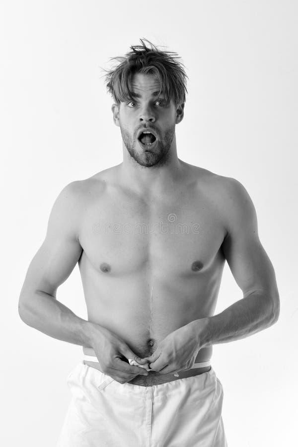 Gezond levensstijl en metingenconcept De kerel stelt in witte broek stock afbeeldingen