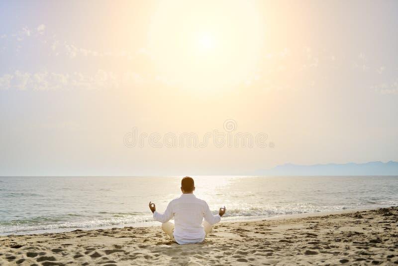 Gezond levensstijlconcept - mens die de oefeningen van de yogameditatie op het strand doen royalty-vrije stock fotografie