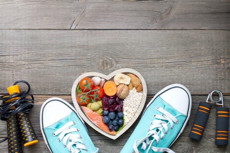 Gezond levensstijlconcept met voedsel in hart en sportenfitness toebehoren stock afbeelding