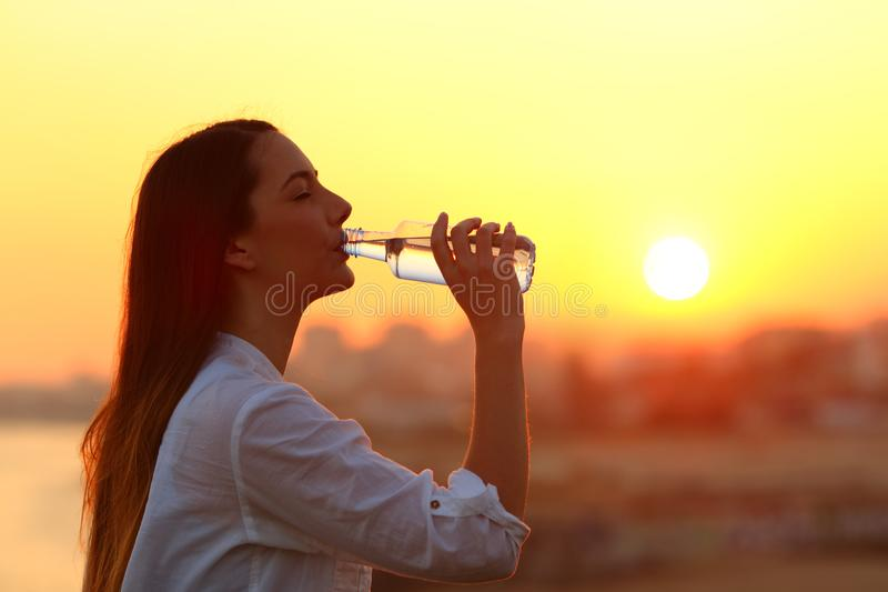 Gezond meisjes drinkwater bij zonsondergang stock afbeelding