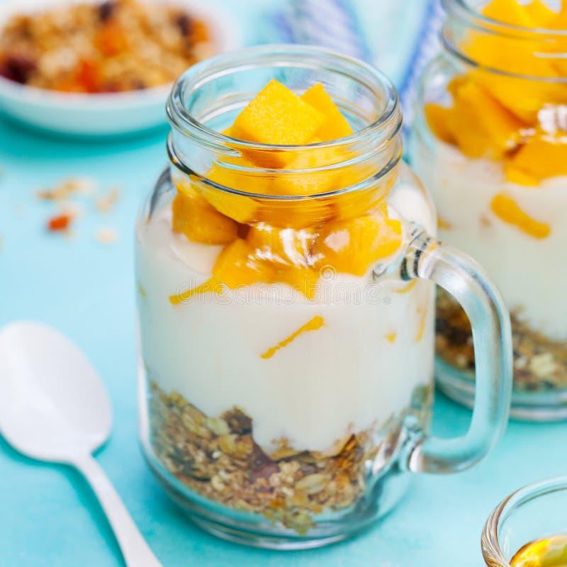 Gezond ontbijt, dessert Vers mangofruit met yoghurt en granola in kruiken Achtergrond voor een uitnodigingskaart of een gelukwens stock foto's