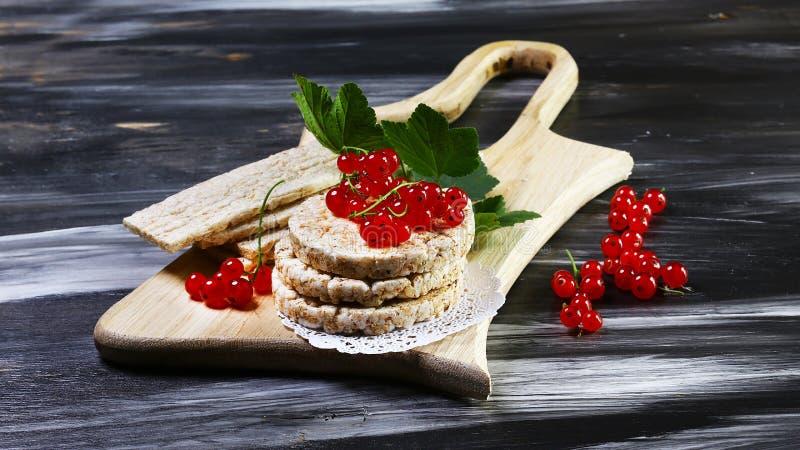 Gezond Ontbijt en een snack van rijstbrood met rode aalbes op een raad, op een houten donkere achtergrond, Exemplaarruimte royalty-vrije stock afbeeldingen